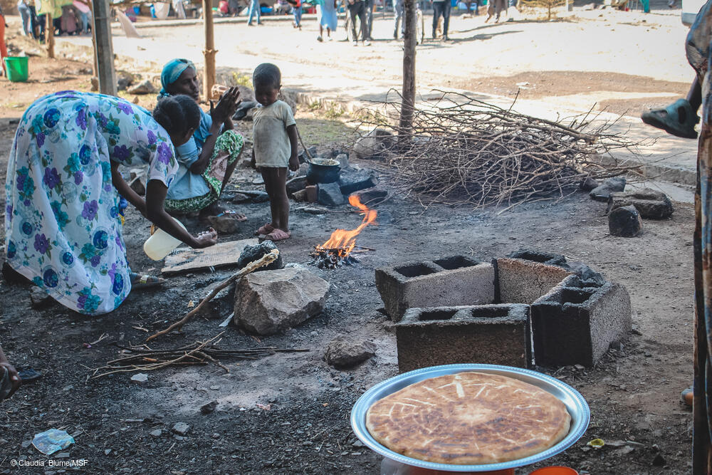 Cooking on makeshift stoves outside. As the only donation most people have received is wheat, they eat bread every day.