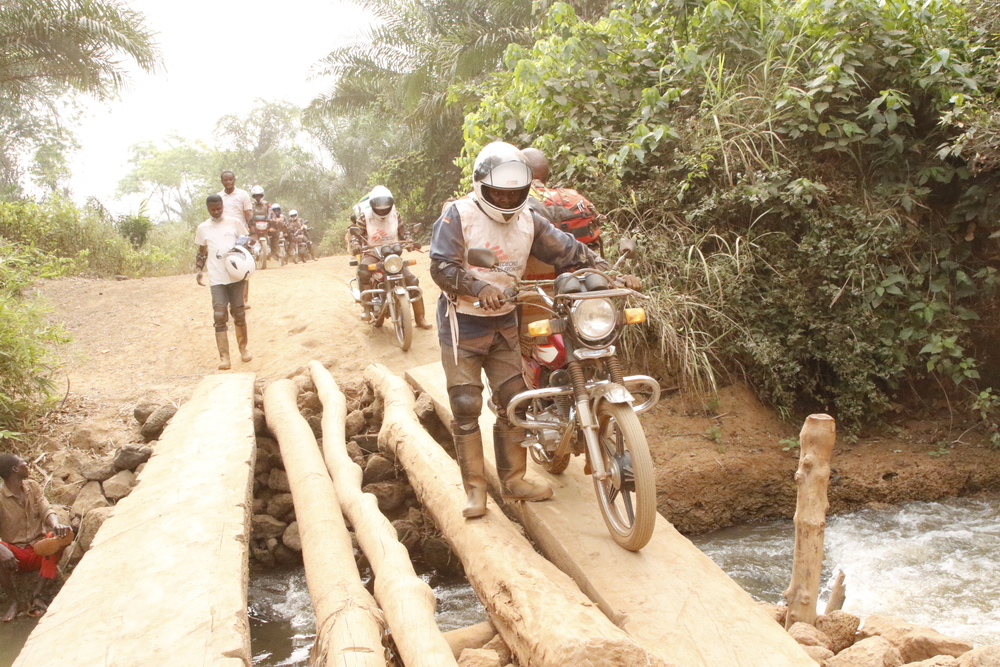 The MSF emergency team crosses a small river in the Bosobolo health zone.