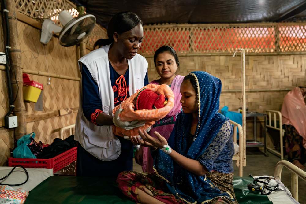 A Rohingya mother and her baby with midwife Christine Akoth in Cox's Bazar. Bangladesh, July 2019.