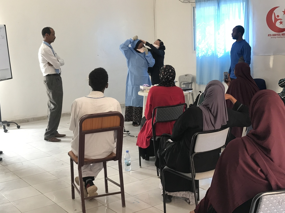 MSF staff show healthcare workers how to wear PPE in Hargeisa