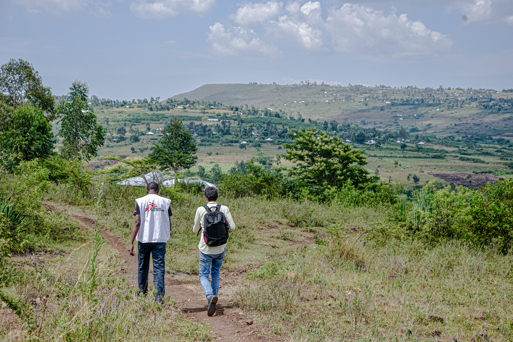 MSF staff walking in the field heading for a call-back during the NHIPS survey.