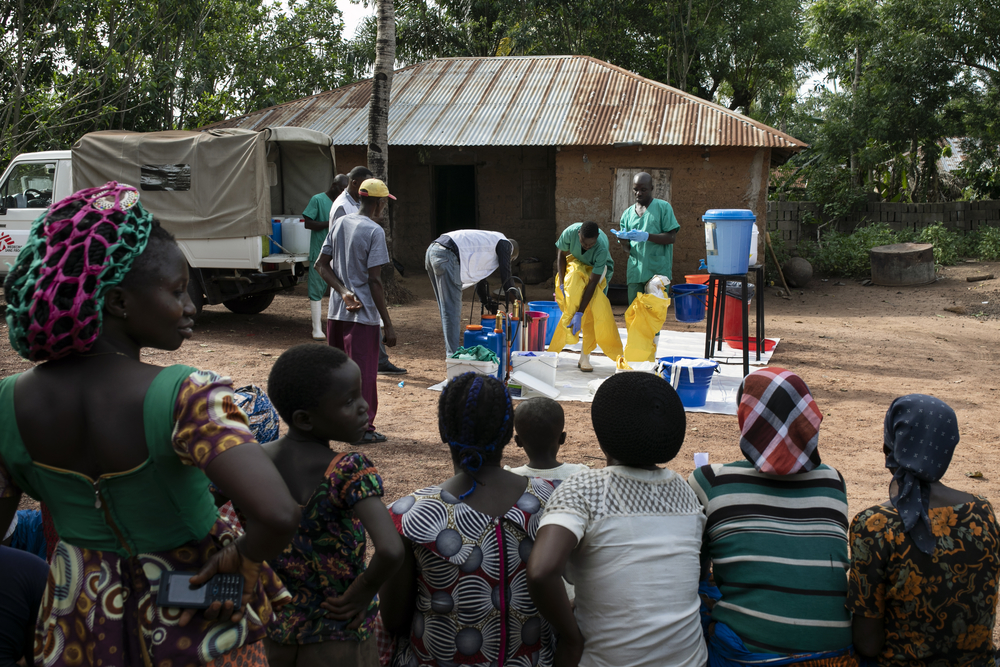 Villagers watch a WatSan prepare for the disinfection of a house in Ndiovu village