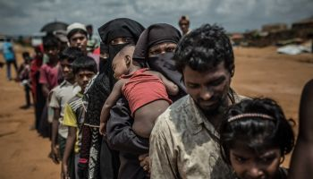 June 2018: A group of Rohingya refugees await assignment to their new homes in in the Kutupalong camp, Cox's Bazar. [© Pablo Tosco/Angular ]