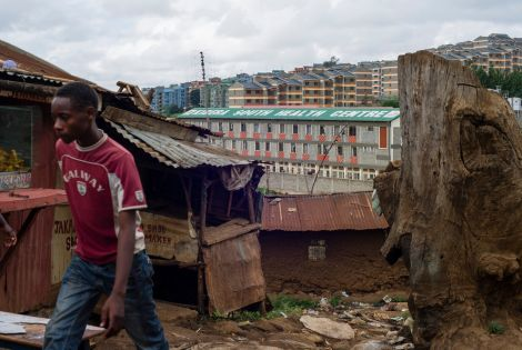 2014: A man walks past a small, tin-roof shop in the Kibera slum, near Kibera South Health Centre