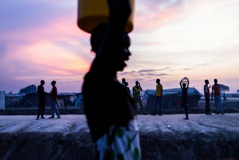 woman walks past a group of young men after collecting water just as the sun set inside the UN Protection of Civilians site in Bentiu. [ © Dominic Nahr / MAPS]
