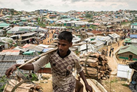 A Rohingya man carries wood through the Kutupalong- Balu Khali mega camp. Cox's Bazar District, Bangladesh. [© Robin Hammond/NOOR ]