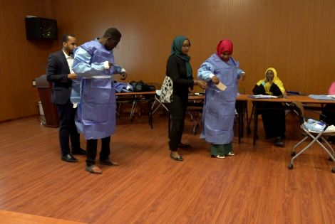 Sudanese healthcare professionals put on personal protection equipment during a training workshop