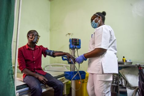 Faith Njeri, an EMT at MSF Lavender House checks vitals of a patient